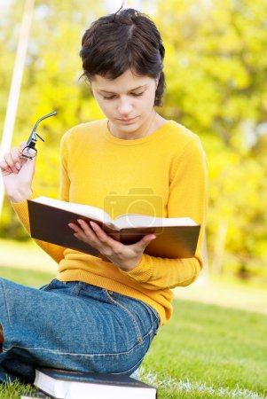 Photo for Young student holding books on autumn background. - Royalty Free Image