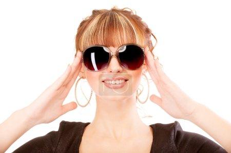 Girl laughs, holding sun glasses