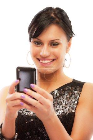Photo pour Charmante fille lit les sms sur le téléphone, isolé sur fond blanc - image libre de droit