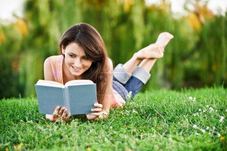 Photo pour Fille-élève se couche sur la pelouse et lit le manuel . - image libre de droit