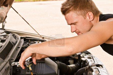 Car mechanician repairs engine