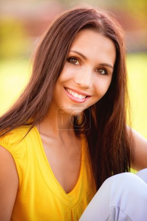 Photo for Portrait of beautiful young woman in yellow vest against green lawn. - Royalty Free Image