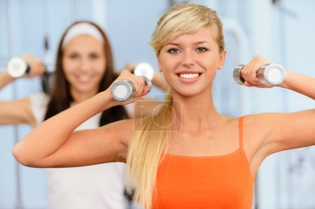 Photo for Two beautiful smiling sportswomen do exercises with dumbbells in big sports hall. - Royalty Free Image