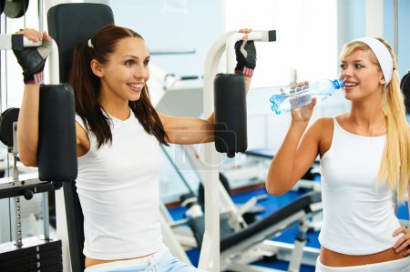 Photo pour Deux jeunes filles dans la salle de gym. l'un est travailler sur machine à bras, deuxième boit l'eau pure. - image libre de droit