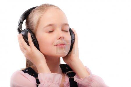 Foto de Colegiala hermosa joven escucha música en los auriculares, aislado sobre fondo blanco. - Imagen libre de derechos