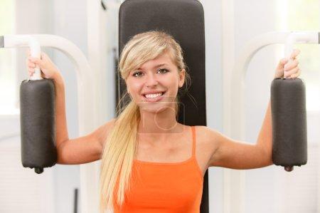 Photo pour Faire blonde magnifique exercice sur appareil musculation - image libre de droit