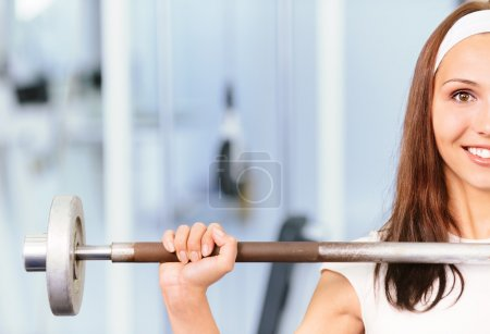Photo for Young woman lifts weight and smiles, against sports hall. - Royalty Free Image