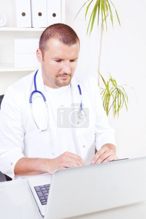 Handsome male doctor working in office