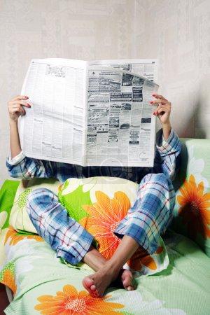 Photo pour Femme méconnaissable à l'intérieur de lecture Journal - image libre de droit