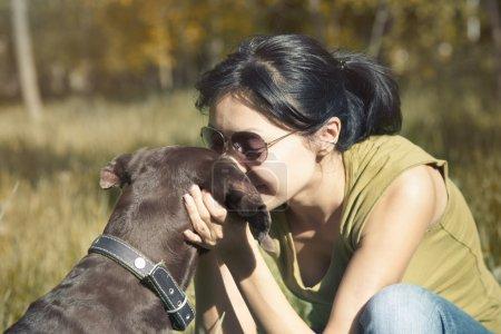 Photo pour Dame heureuse en plein air s'embrasser et de choyer son chien. lumière du soleil de printemps utilisé et croix-traité des couleurs ajoutées - image libre de droit