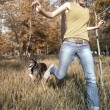 Happy young girl outdoors running with dog in the ...