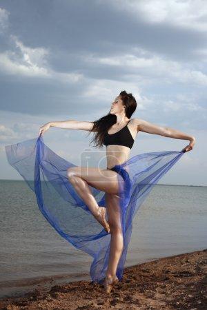 Photo pour Élégante dame dansant à la plage avant la tempête de pluie. Photo verticale - image libre de droit