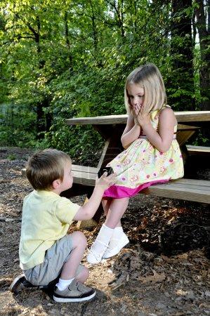 Photo pour Un petit garçon qui demande en mariage une petite fille - image libre de droit
