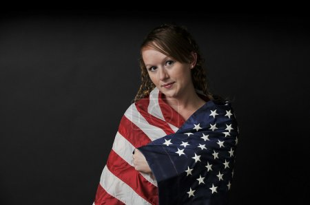 Photo for A beautiful young woman wrapped in a flag. - Royalty Free Image