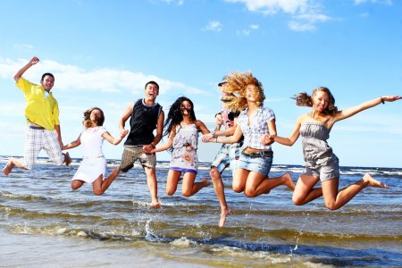 Happy teenagers playing at the sea