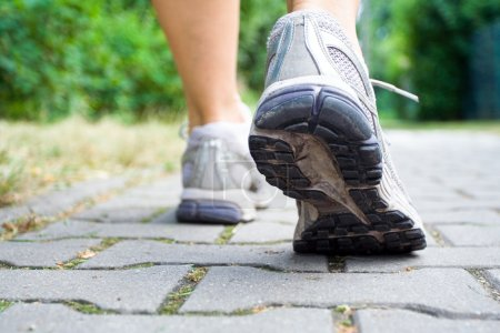 Photo for Woman walking on sidewalk, sport shoes close-up - Royalty Free Image