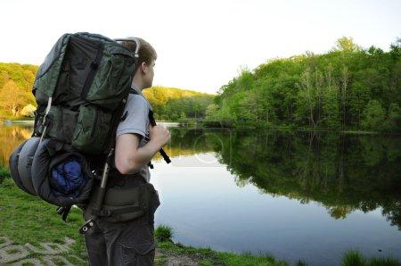 Teenage hiker standing by Sunrise Lake on the Patr...