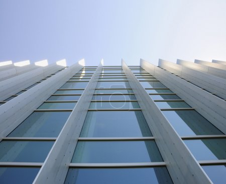 Exterior windows of modern commercial office building looking up