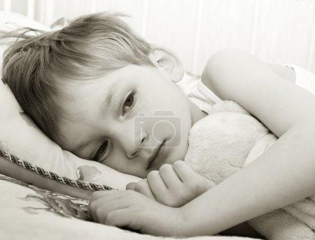 enfant triste dans son lit