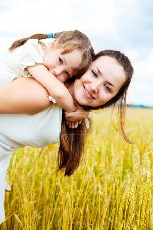 Photo pour Belle jeune maman et sa fille dans le champ de blé sur une journée ensoleillée (mise au point sur l'enfant) - image libre de droit
