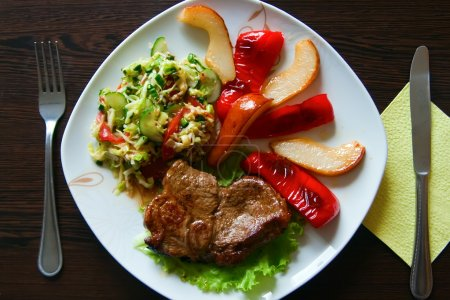 Photo for Fried steak served with paprika, pear and fresh vegetable salad - Royalty Free Image