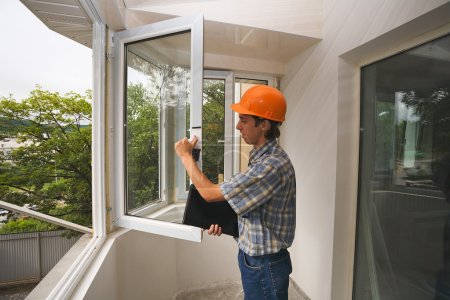 Photo for The building inspector checks quality of installation of new windows. - Royalty Free Image