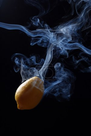 Photo for Yellow lemon enveloped by smoke on a black background - Royalty Free Image