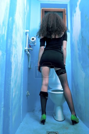 Young lady standing by toilet bowl in neglected, d...