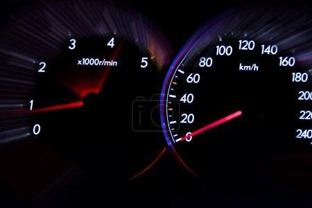 Car dashboard gauges illuminated at night, motion ...