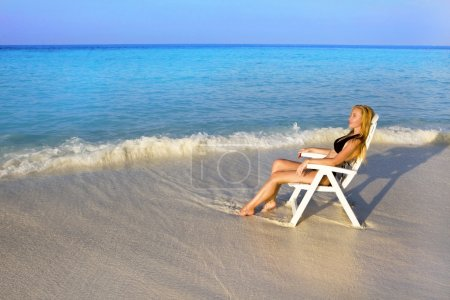 Woman tans in beach chair in ocean