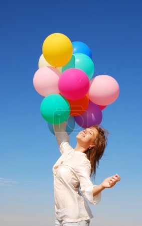 Photo for Young happy woman with balloons over sky - Royalty Free Image