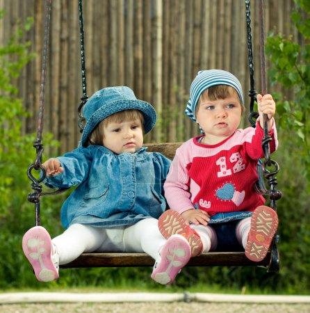 Foto de Dos niños en los columpios en el parque - Imagen libre de derechos
