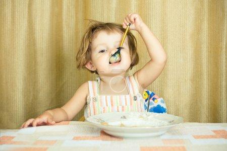 Little girl eats porridge