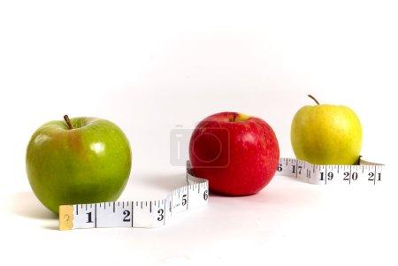 Photo pour Pommes entourées d'une bande de mesure, concept de perte de poids - image libre de droit