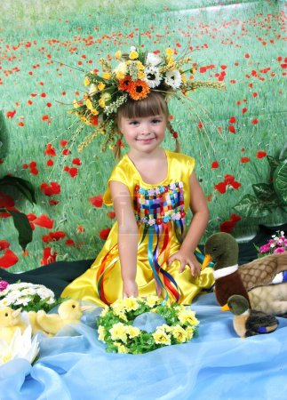 Girl in national costume puts a wreath on the water