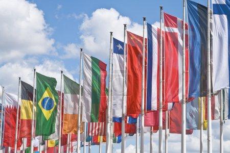 Photo pour De nombreux drapeaux nationaux contre un ciel nuageux beuatiful - image libre de droit