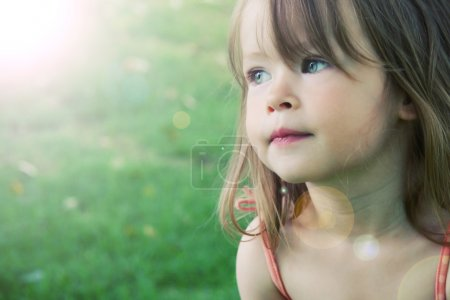 Adorable little girl taken closeup outdoors in sum...