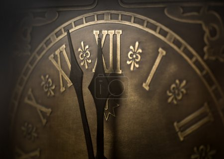 Photo for Old clock with roman numerals. Selective focus on number XII and minute hand. Intentional vignetting. - Royalty Free Image