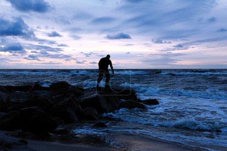 Photo for Man standing on a stony sea shore and observing sunset - Royalty Free Image