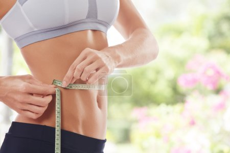 Close up view of young beautiful woman measuring h...