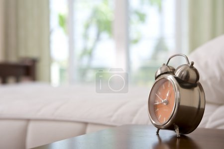 Photo for Close up view of alarm-clock in morning bedroom environment - Royalty Free Image