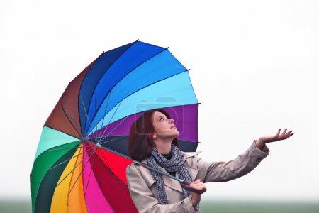 Girl with umbrella on field.