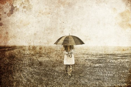 Girl with umbrella at field. Photo in old image style.