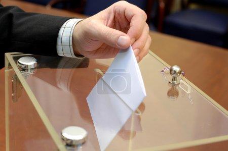 Photo pour Image d'une urne et d'une main mettant un bulletin blanc à l'intérieur, concept d'élection, concept de vote - image libre de droit