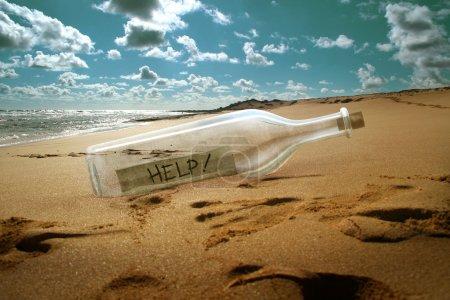 Photo pour Message d'aide dans une bouteille sur la plage - image libre de droit