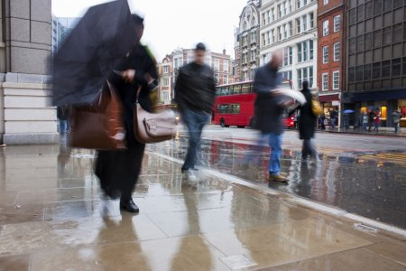 Busy london commuters in the pouring rai