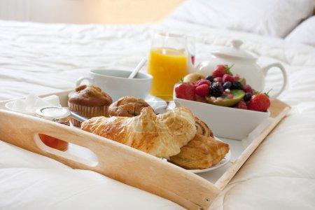 Photo pour Petit déjeuner au lit avec fruits et pâtisseries sur un plateau - image libre de droit