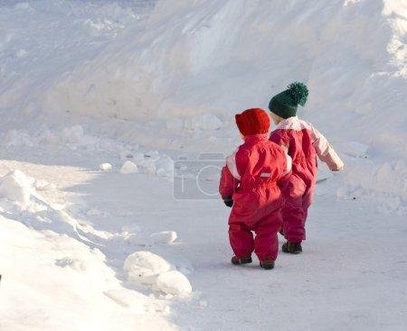 Photo pour Enfants en vêtements d'hiver épais marchant sur une route enneigée - image libre de droit