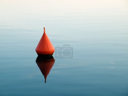 Single red buoy on a calm sea surface....