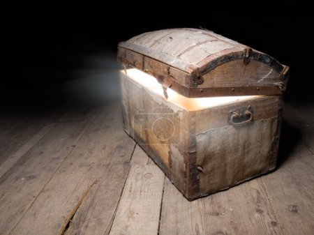 Photo for Old wooden treasure chest with strong glow from inside. - Royalty Free Image
